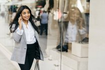 Smiling businesswoman talking on smartphone and walking along shop windows — Stock Photo