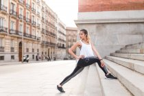 Sportive woman with earphones stretching legs on stairs steps at city scene — Stock Photo