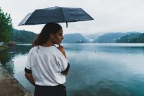 Woman standing on lake shore with umbrella and looking over shoulder — Stock Photo