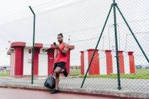 Спортсмен в наушниках опирается на проволочный забор и просматривает смартфон — стоковое фото