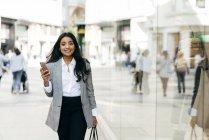 Vorderansicht einer eleganten Frau mit Smartphone, die neben Schaufenstern läuft und in die Kamera blickt — Stockfoto