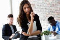 Ritratto di giovane donna d'affari che guarda la macchina fotografica in ufficio — Foto stock