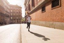 Blonde girl in sportswear jogging on sidewalk — Stock Photo