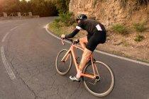 Задній вид велосипедиста їзда велосипеді уздовж асфальтована дорога біля глинистий обрив сонячний день. — стокове фото