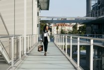Portrait de femme élégante en vêtements élégants marchant sur le passage du balcon et regardant de côté — Photo de stock