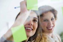 Ritratto di donna sorridente di affari rendendo nota su adesivo alla parete di vetro. — Foto stock