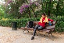 Спортивна дівчина з пляшку води і рушник на плечах, сидячи в парку і перегляду смартфон — стокове фото