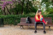 Sportive girl sitting on park bench with energetic drink and taking selfie — Stock Photo