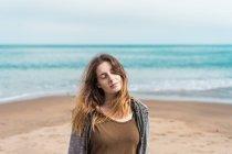 Porträt einer Frau, die mit geschlossenen Augen vor dem Hintergrund des blauen Ozeans posiert — Stockfoto