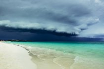 Landscape of white sandy beach and turquoise ocean water under stormy dark cloud. — Stock Photo