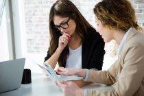 Ritratto di due donne di affari usando tavoletta digitale durante la discussione in ufficio — Foto stock
