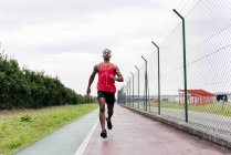 Front view of man wearing headphones jogging along fence — Stock Photo