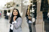 Веселий жінка, що носить елегантний куртка позують поблизу вітрині — стокове фото