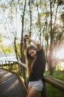 Bionda giovane donna appoggiata su ringhiera ponte di legno e in posa per la fotocamera nella giornata di sole . — Foto stock