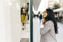 Side view of smiling woman wearing jacket looking at shop window — Stock Photo
