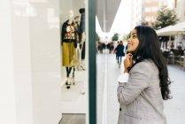 Вид збоку усміхається жінка, носять куртки, дивлячись на вітрині — стокове фото