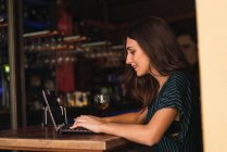 Side view of smilig woman typing on laptop in cafe — Stock Photo
