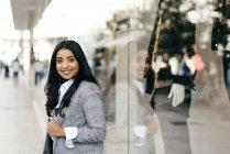 Eleganter Geschäftsmann posiert in Schaufensternähe und blickt in die Kamera — Stockfoto