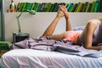 Обтинання жінка, лежачи на ліжку, за книжкову полицю — стокове фото