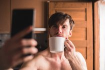 Man with cup and doing selfie in kitchen. — Stock Photo