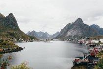 Impresionante vista del lago de la montaña y el pequeño pueblo en la costa en día nublado. - foto de stock