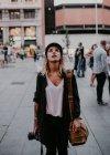 Mulher com a câmera nas mãos, parado na rua e olhando para cima — Fotografia de Stock