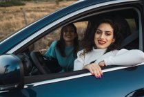 Smiling women in car looking at camera — Stock Photo
