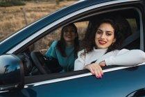 Улыбаясь женщин в автомобиле, глядя на камеру — стоковое фото