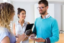 Sonriente grupo de gente de negocios hablando entre sí en la oficina moderna . - foto de stock