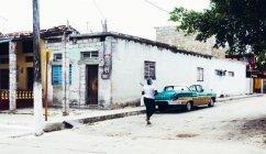 CUBA - 27 DE AGOSTO DE 2016: Vista trasera de la mujer caminando por la calle pobre de la ciudad con edificios en mal estado . - foto de stock