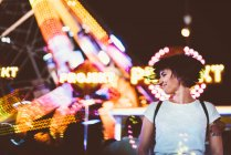 Young woman shaking hair happily on background of glowing lights of amusement park in night. — Stock Photo