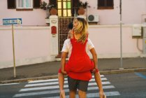 Man carrying young girl on back and crossing road — Stock Photo
