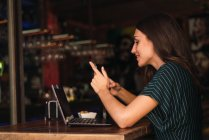 Vue latérale de la femme utilisant un smartphone au café — Photo de stock