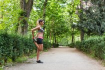 Вид збоку fit жінки в спортивному одязі розтягування ногу шлях в зеленому парку — стокове фото