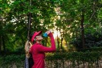 Seitenansicht der blonden Sportlerin, die nach dem Training Wasser trinkt — Stockfoto