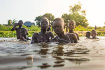 BENIN, AFRICA - AUGUST 31, 2017: Group of kids swimming in river and looking at camera on tropical background. — Stock Photo