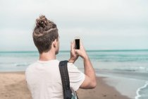 Rear view of man taking picture of beach on smartphone — Stock Photo