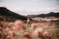 Vue latérale de la femme qui marche sur le champ sur fond de montagnes au soleil. — Photo de stock
