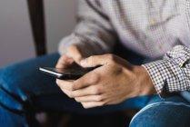Crop mani maschili con smartphone su scala — Foto stock