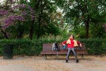 Fille sportive avec bouteille d'eau et une serviette sur les épaules reposant sur le banc dans le parc — Photo de stock
