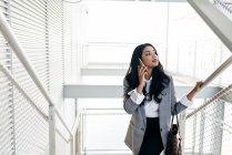 Mulher de negócios elegante subindo escadas e falando no smartphone — Fotografia de Stock