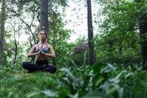 Sportliche Mädchen sitzen auf Boden und Durchführung Yoga Asana unter Wald — Stockfoto