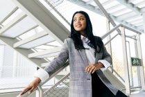Retrato de mulher elegante em jaqueta apoiada no corrimão na passagem escadas — Fotografia de Stock