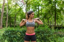 Sporty girl warming up shoulders in city park — Stock Photo