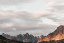 Пейзаж солнечных высоких вершин над облачным небом — стоковое фото