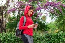Porträt eines sportlichen Mädchens, das mit dem Smartphone über einen blühenden Baum im Park surft — Stockfoto