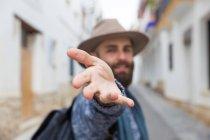 Uomo barbuto in cappello che guarda l'obbiettivo e gesturing Seguimi — Foto stock