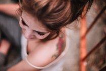 Vue de dessus des femmes avec dos tatoué assis et regardant de côté — Photo de stock