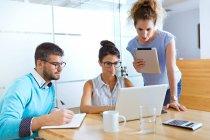 Grupo de gente de negocios en la mesa usando el ordenador portátil mientras se reúnen - foto de stock