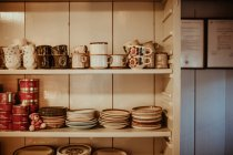 Wooden shelves with stacks of  dinnerware at kitchen — Stock Photo